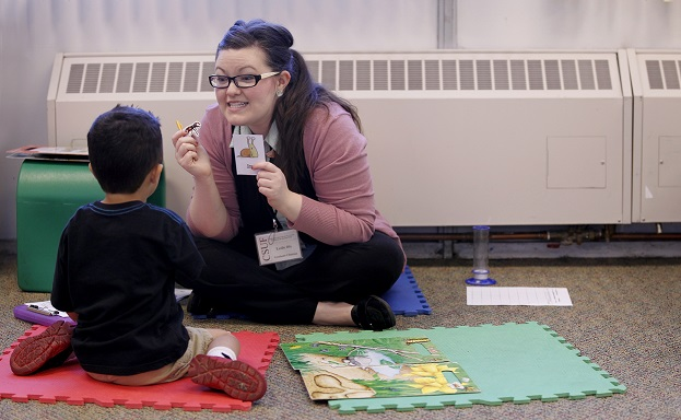 Graduate clinician providing speech therapy to a child.